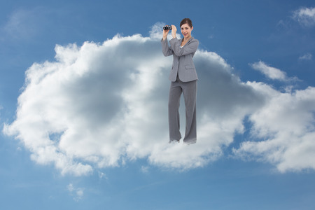 Businesswoman posing with binoculars against cloudy sky photo