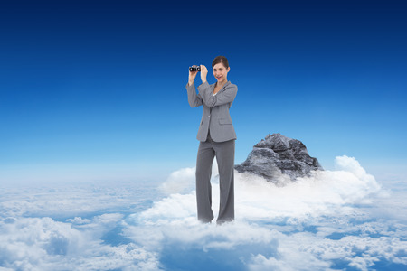 Businesswoman posing with binoculars against mountain peak through the clouds photo