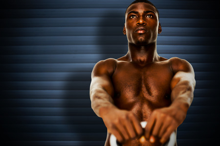 kettle bell: Shirtless fit young man lifting kettle bell against grey shutters Stock Photo
