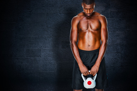 kettle bell: Shirtless fit young man lifting kettle bell against black background