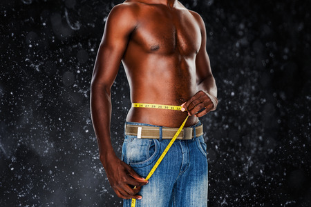 measuring waist: Mid section of a fit shirtless man measuring waist against black background