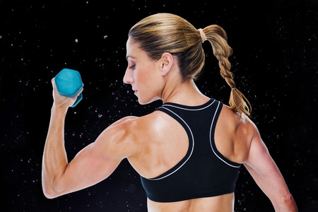 lean out: Female bodybuilder holding a dumbbell against black background
