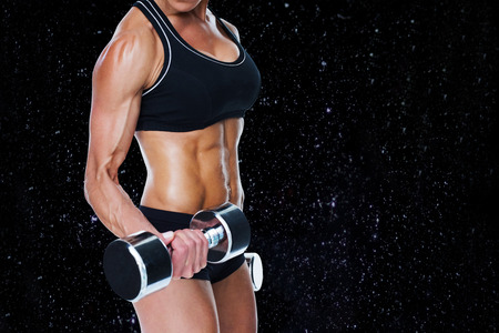 lean out: Female bodybuilder working out with large dumbbells mid section against black background