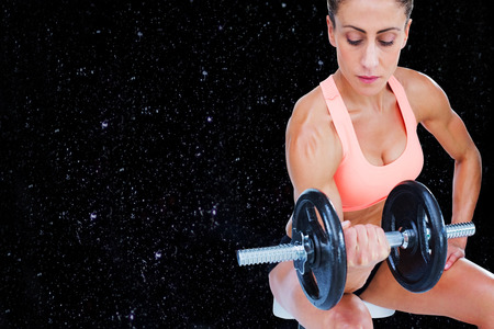 lean out: Strong woman doing bicep curl with large dumbbell against black background