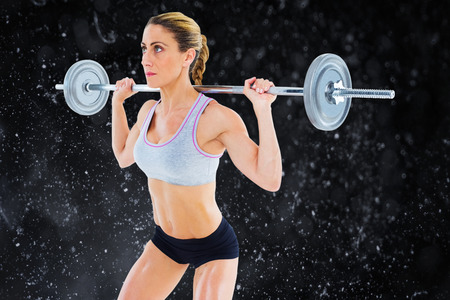 lean out: Strong female crossfitter lifting barbell behind head against black background Stock Photo