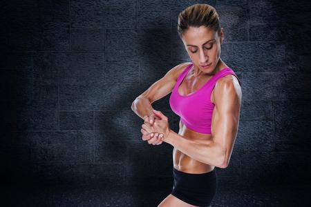 flexing: Female bodybuilder flexing in pink sports bra against black background Stock Photo