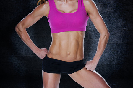 lean on hands: Female bodybuilder posing in pink sports bra and shorts mid section against black background Stock Photo
