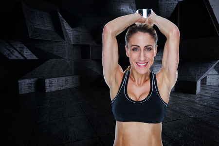 lean out: Female happy bodybuilder working out with large dumbbell behind head against dark room Stock Photo