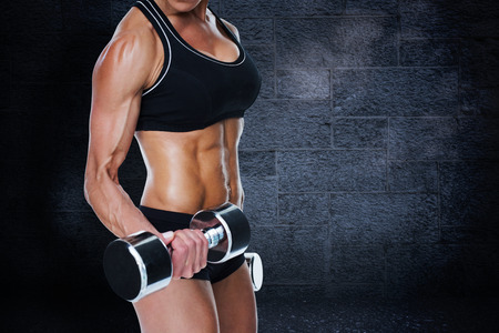 female person: Female bodybuilder working out with large dumbbells mid section against black background