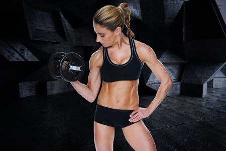 lean out: Female bodybuilder holding large black dumbbell with arm up looking at bicep against dark room Stock Photo