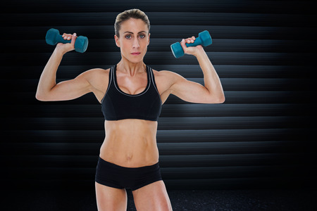 lean out: Female bodybuilder holding two dumbbells with arms up against black background