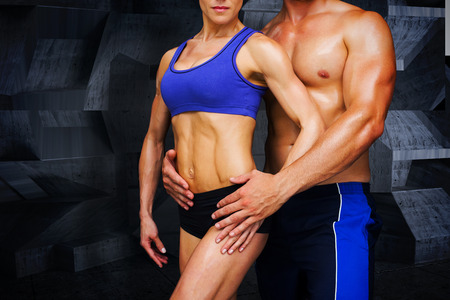 male female: Bodybuilding couple against dark room