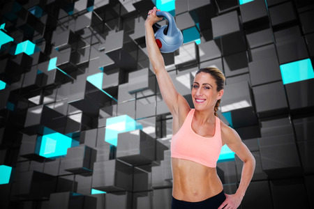 lean out: Female blonde crossfitter lifting kettlebell above head smiling at camera against blue and black tile design Stock Photo
