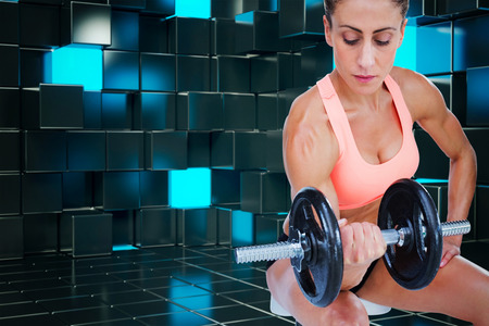 lean out: Strong woman doing bicep curl with large dumbbell against blue and black tile design Stock Photo