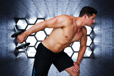 lean out: Bodybuilder lifting dumbbell against hexagon room Stock Photo