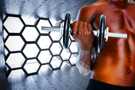 abdominal wall: Mid section of fit shirtless man holding dumbbell against hexagon room Stock Photo