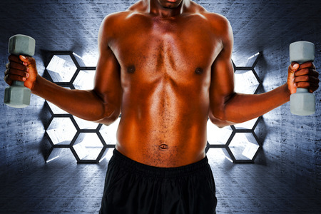 abdominal wall: Mid section of fit shirtless man lifting dumbbells against hexagon room