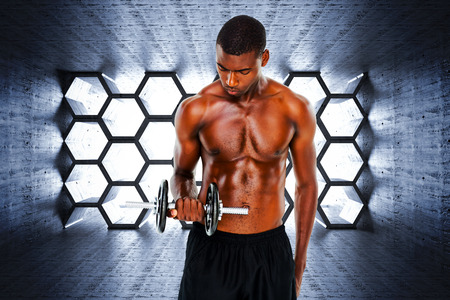 abdominal wall: Serious fit shirtless young man lifting dumbbell against hexagon room Stock Photo