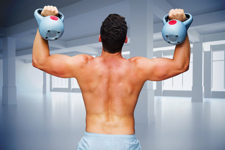 abdominal wall: Bodybuilder holding kettlebell against white room with windows