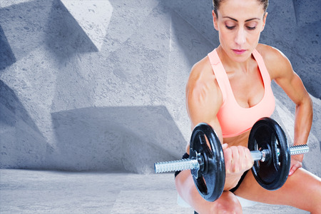 lean out: Strong woman doing bicep curl with large dumbbell against grey angular background