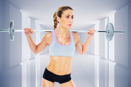 lean out: Strong female crossfitter lifting barbell behind head against digitally generated room