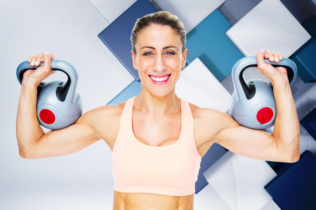 lean out: Happy female crossfitter lifting kettlebells looking at camera against blue and white tile design