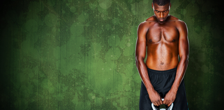 kettle bell: Shirtless fit young man lifting kettle bell against green paint splashed surface