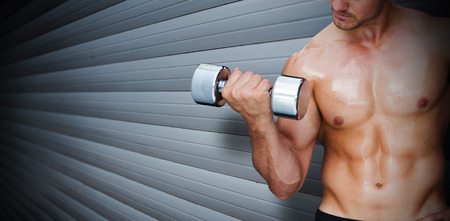 lean out: Bodybuilder lifting dumbbell against grey shutters