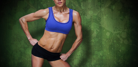 Female bodybuilder against green paint splashed surface Stock Photo