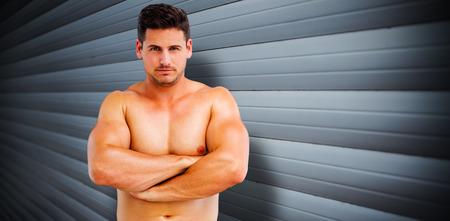 shutters: Bodybuilder posing against grey shutters