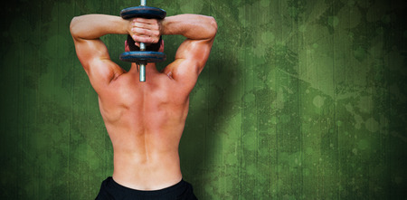 lean out: Bodybuilder lifting dumbbell against green paint splashed surface Stock Photo