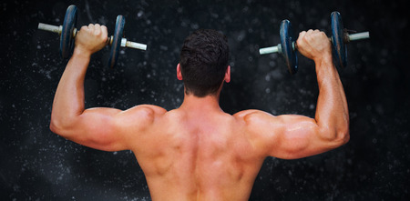 lean out: Bodybuilder lifting dumbbells against black background Stock Photo