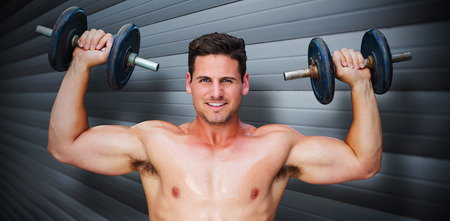 lean out: Bodybuilder lifting dumbbells against grey shutters Stock Photo