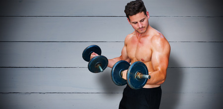 lean out: Bodybuilder lifting dumbbell against painted blue wooden planks Stock Photo
