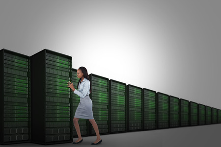 Portrait of a young businesswoman pushing a panel against server tower photo