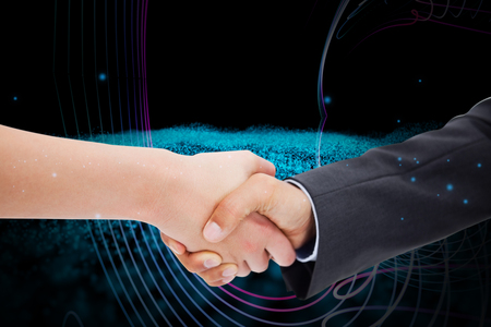 against abstract: Close up of a handshake against abstract glowing black background Stock Photo