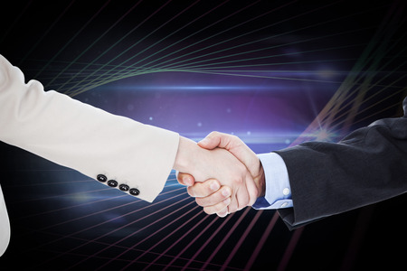 teamworking: Smiling business people shaking hands while looking at the camera against black background with spark