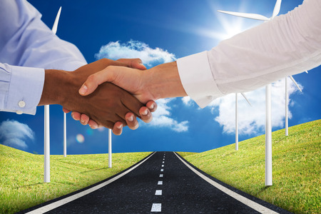 mid distance: Close-up shot of a handshake in office against road leading out to the horizon with wind turbines either side Stock Photo
