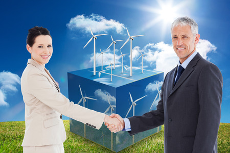 teamworking: Smiling business people shaking hands while looking at the camera against wind turbines on cube showing more wind turbines