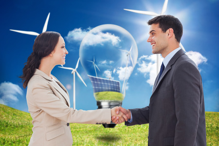 happy business team: Future partners shaking hands against light bulb showing solar panels and turbines in a field with wind turbines Stock Photo