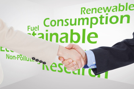 nonpolluting: Smiling business people shaking hands while looking at the camera against creative image of green economy concept