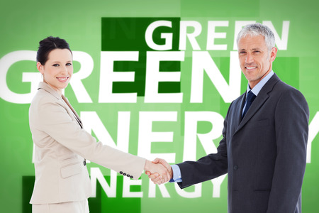 teamworking: Smiling business people shaking hands while looking at the camera against creative image of green energy concept
