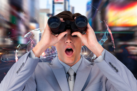 visions of america: Suprised businessman looking through binoculars against global technology background in blue Stock Photo