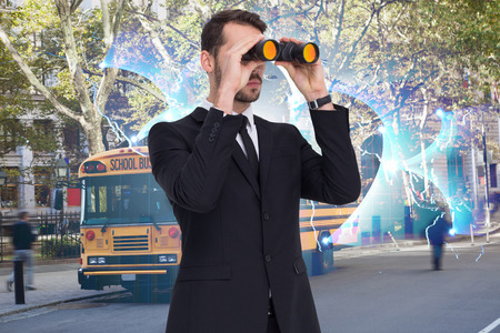 digitally: Elegant businessman standing and using binoculars  against global business graphic in blue Stock Photo