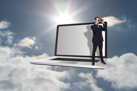 using binoculars: Elegant businessman standing and using binoculars  against sky Stock Photo