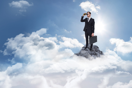 using binoculars: Businessman holding a briefcase while using binoculars  against mountain peak through the clouds