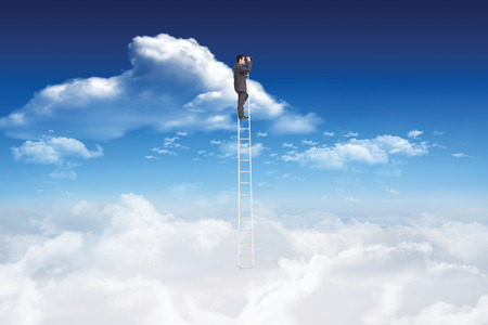 ladder: Businessman standing on ladder using binoculars against bright blue sky with clouds