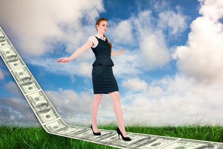 balancing act: Businesswoman doing a balancing act against green grass under blue sky