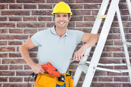 step ladder: Technician holding drill machine while leaning on step ladder against red brick wall Stock Photo