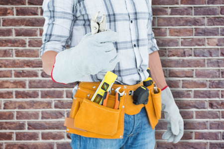 waist belt: Technician with tool belt around waist holding pliers against red brick wall Stock Photo